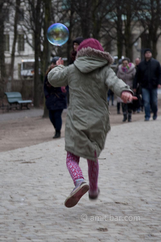 Berlin: Soap bubble. A girl is chasing a soap bubble