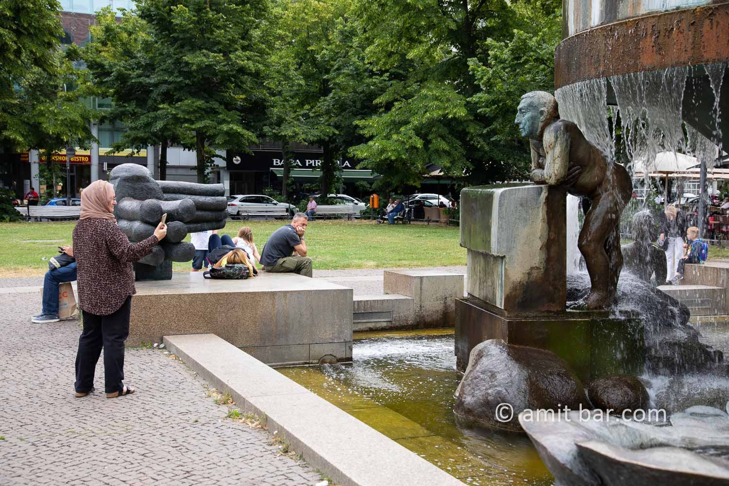 Can I help, you, Miss?: A woman is taking a photo of sculpture