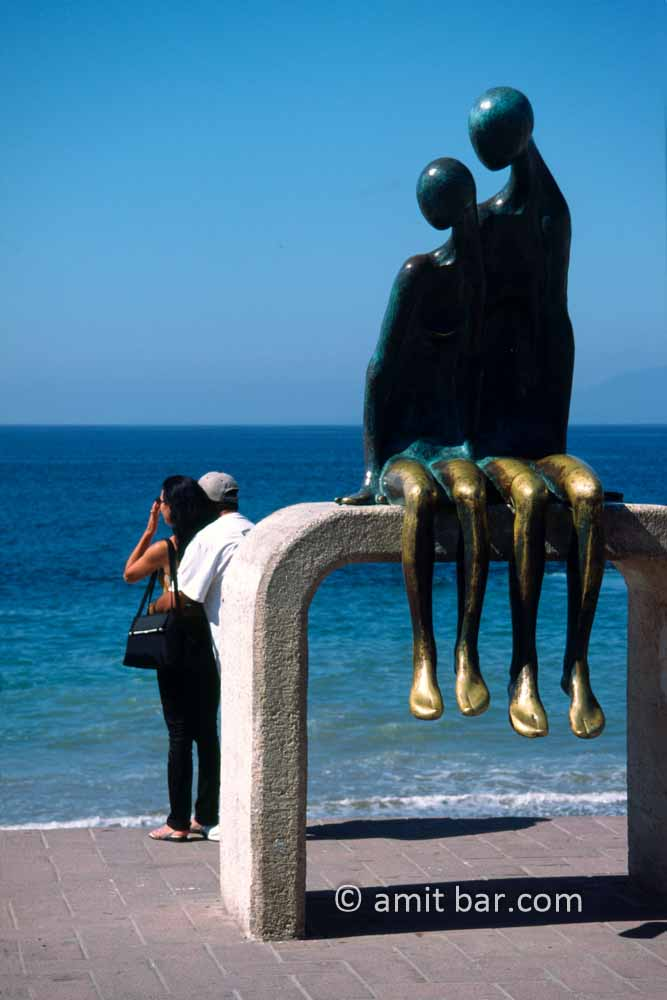 Couples: A sculpture couple looking to a real couple on the promenade of Puerto Vallarta, Mexico