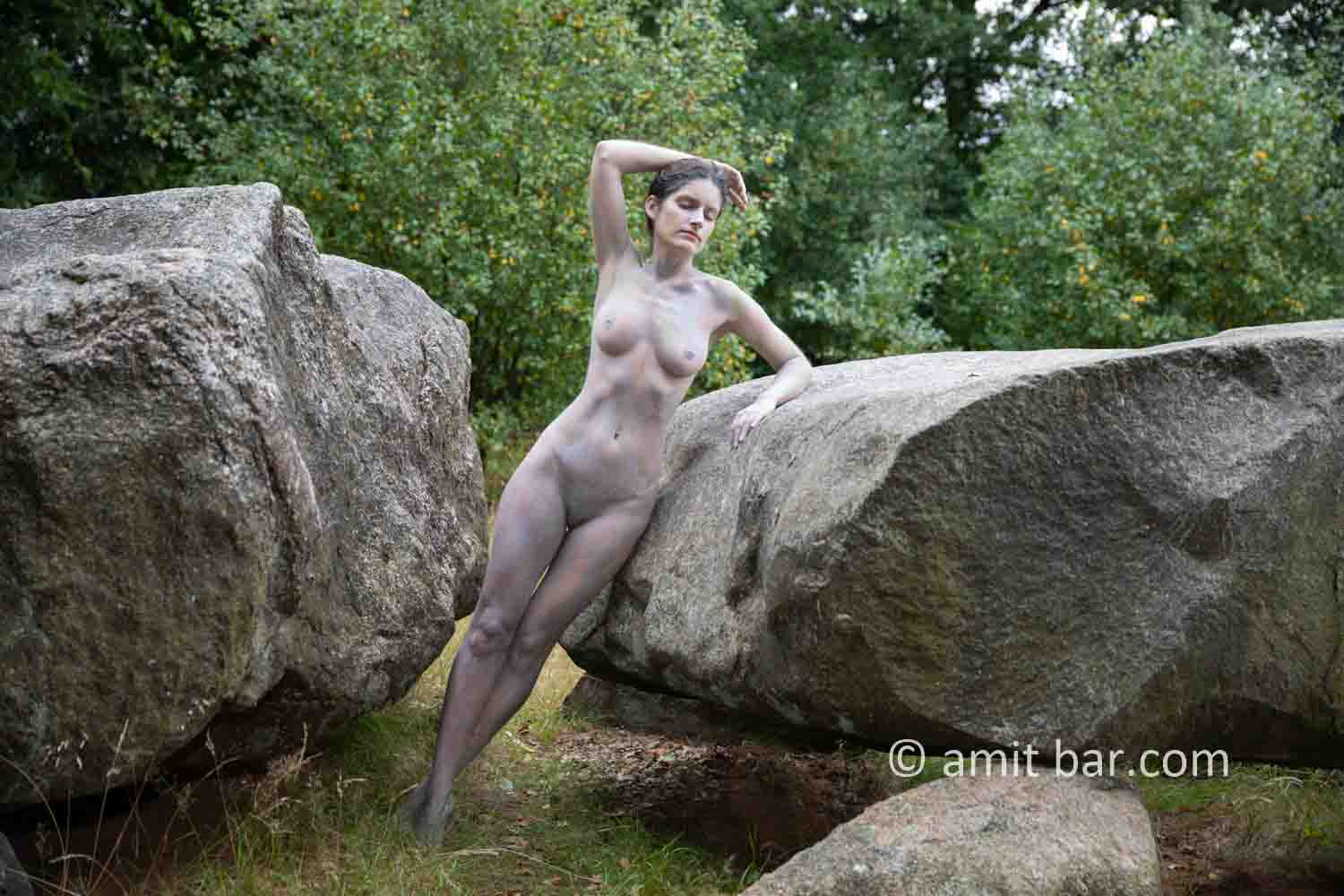 Dolmen woman body-painting II: body painted Elle is walking and laying around and on the huge stones of the dolmen at Drenthe, The Netherlands