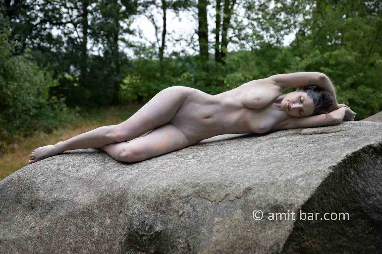 Dolmen woman body-painting IV: body painted Elle is walking and laying around and on the huge stones of the dolmen at Drenthe, The Netherlands