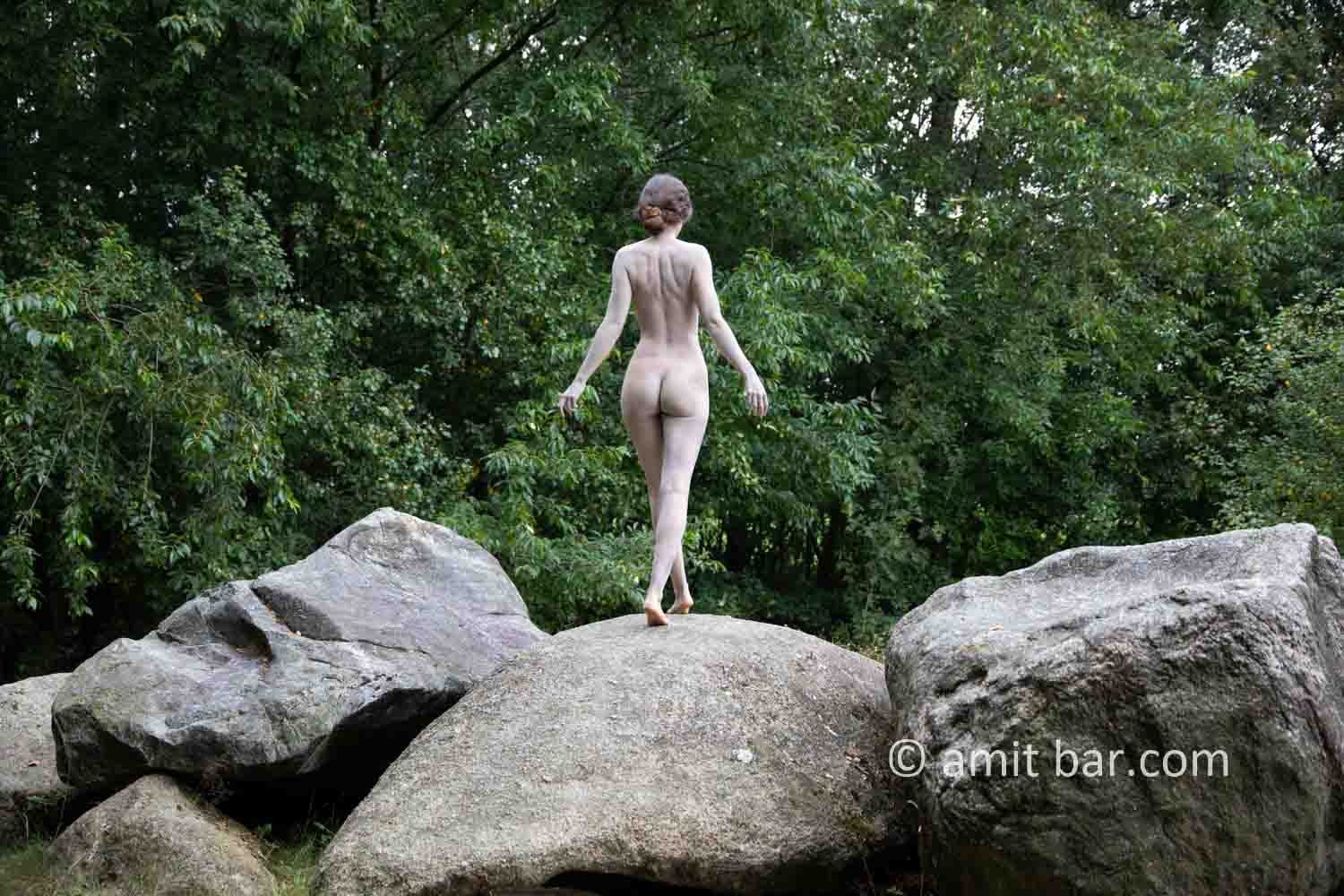 Dolmen woman body-painting VI: body painted Elle is walking and laying around and on the huge stones of the dolmen at Drenthe, The Netherlands