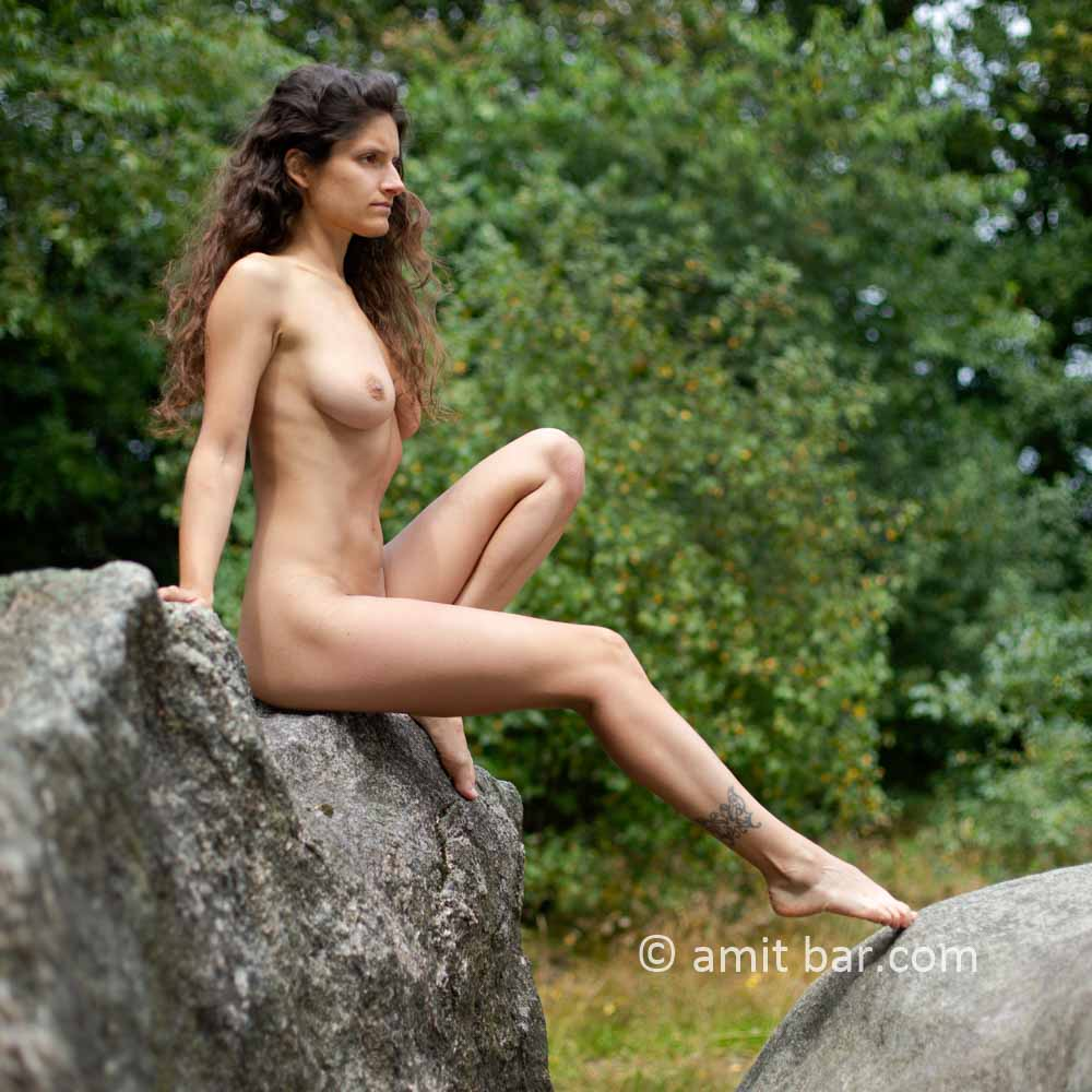 Dolmen woman I: Elle is walking and laying around and on the huge stones of the dolmen at Drenthe, The Netherlands