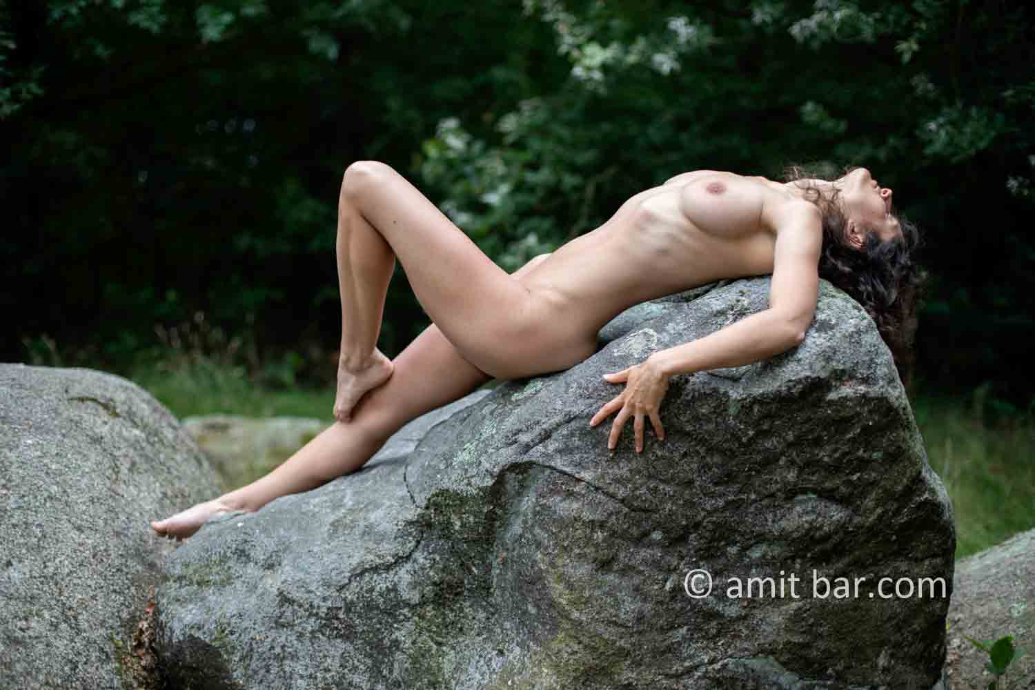Dolmen woman IV: Elle is walking and laying around and on the huge stones of the dolmen at Drenthe, The Netherlands
