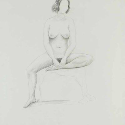 Nude woman sitting on a low box